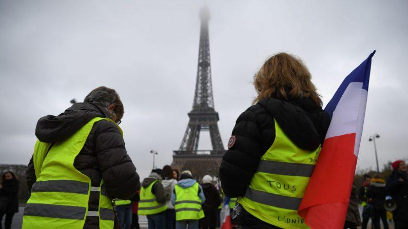 """Una mujer que lleva un """"chaleco amarillo"""" (gilets jaunes) sostiene una bandera francesa frente a la Torre Eiffel, en París, el 20 de enero de 2019, mientras participan en una reunión para protestar contra el gobierno y la violencia policial. (ERIC FEFERBERG / AFP / Getty Images)"""