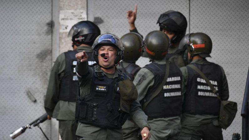 Miembros de la Guardia Nacional Bolivariana increpan a manifestantes cerca de la sede de la Guardia Nacional Bolivariana en Caracas, Venezuela, el 21 de enero de 2019. (YURI CORTEZ/AFP/Getty Images)