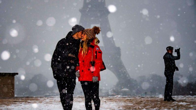 Una pareja es fotografiada frente a la Torre Eiffel mientras cae nieve sobre París el 23 de enero de 2019. (Foto de Lionel BONAVENTURE / AFP) (El crédito de la foto debe ser LIONEL BONAVENTURE/AFP/Getty Images)