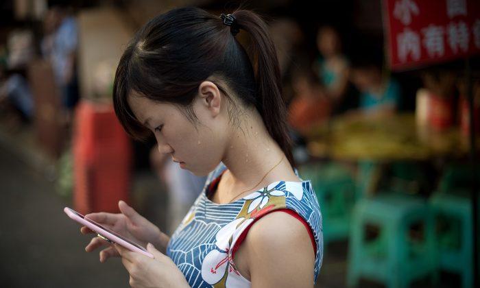 Una joven mira su teléfono inteligente en la ciudad de Chongqing, el 24 de agosto de 2016. (NICOLAS ASFOURI/AFP/Getty Images)