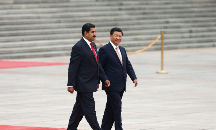 El mandatario chino Xi Jinping (der.) acompaña al dictador de Venezuela, Nicolás Maduro (izq.), a una guardia de honor durante una ceremonia de bienvenida frente al Gran Salón del Pueblo en Beijing el 22 de septiembre de 2013. (Lintao Zhang/Getty Images)