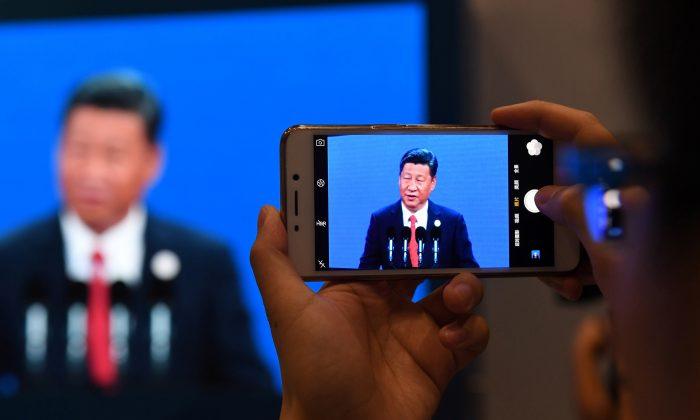 Un periodista toma una foto de una transmisión en vivo del mandatario chino Xi Jinping hablando en Beijing, el 14 de mayo de 2017. (GREG BAKER/AFP/Getty Images)