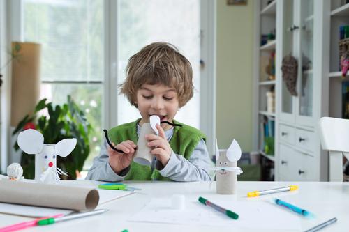 Niño pequeño juega con juguetes caseros de papel hechos por él mismo.  (Shutterstock)