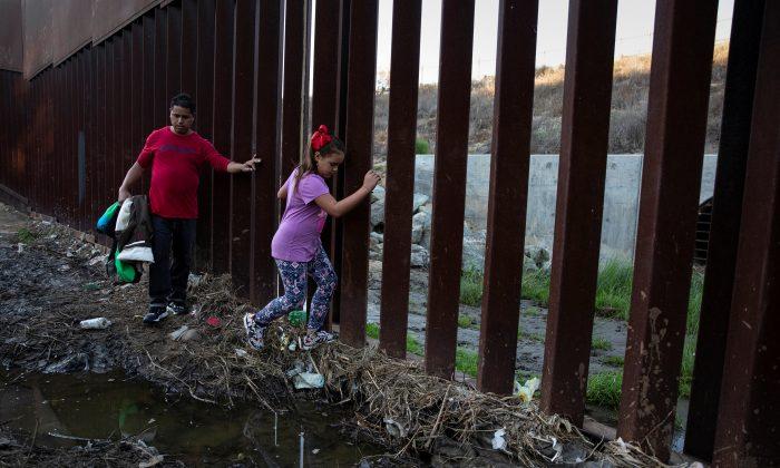 Tony Mauricio Arita, 33, y su hija Andrea Nicole, 10, de Honduras, parte de una caravana de miles  proveniente de América Central, intentando llegar a Estados Unidos, caminan a lo largo de un muro fronterizo antes de cruzar ilegalmente desde México a EE. UU., en Tijuana, México, 4 de diciembre de 2018. (Alkis Konstantinidis/Reuters)