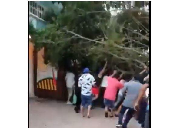 vecinos colaboran para sacar a turistas atrapados bajo un árbol derribado por rachas de viento en Playa del Carmen (Captura de vídeo)