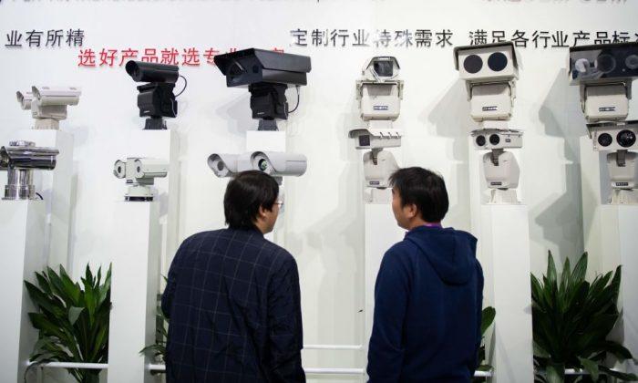 Los visitantes observan las cámaras de seguridad de inteligencia artificial que utilizan tecnología de reconocimiento facial en la 14ª Exposición Internacional de China sobre Seguridad y Protección Pública de China en el Centro Internacional de Exposiciones de China en Beijing, el 24 de octubre de 2018. (Nicolas Asfouri/AFP/Getty Images)