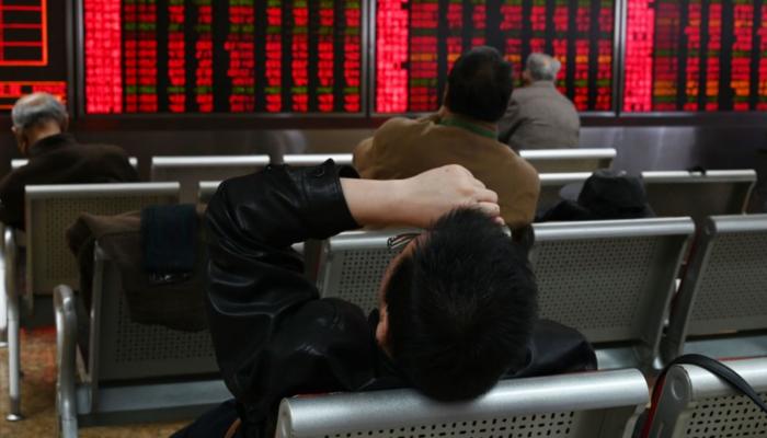 Un hombre descansa frente a las pantallas que muestran precios de acciones en una empresa de títulos valores en Beijing, 21 de enero de 2019. (GREG BAKER/AFP/Getty Images)