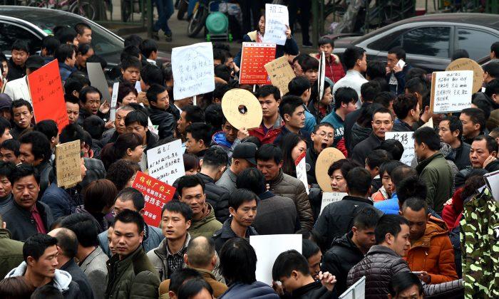 Aspirantes a conseguir un trabajo observan la información de reclutamiento que se muestra en un mercado laboral en Yiwu, China, el 19 de febrero de 2016. (VCG/VCG vía Getty Images)