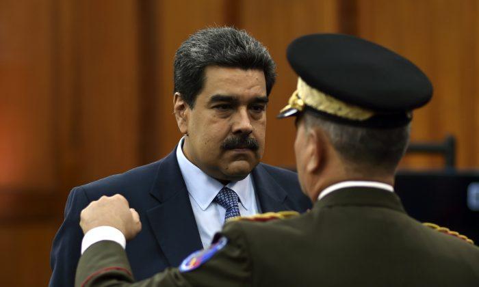El dictador de Venezuela, Nicolás Maduro, habla con el ministro de Defensa Vladimir Padrino en el palacio presidencial de Miraflores en Caracas, Venezuela, el 9 de enero de 2018. (Yuri Corteza/AFP/Getty Images)