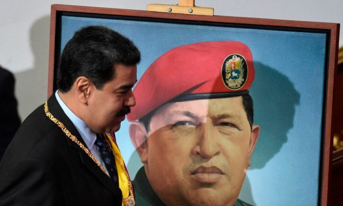 El dictador venezolano Nicolás Maduro pasa junto a un retrato del difunto Hugo Chávez cuando llega a hablar ante la Asamblea Constituyente, en el Palacio Legislativo Federal en Caracas el 14 de enero de 2019. (Federico Parra/AFP/Getty Images)