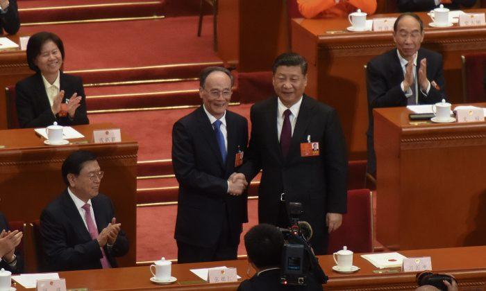 El mandatario chino Xi Jinping (der) y el vice chino Wang Qishan (2do izq) se saludan en el Gran Salón del Pueblo en Beijing, China el 17 de marzo de 2018. (Etienne Oliveau/Getty Images)
