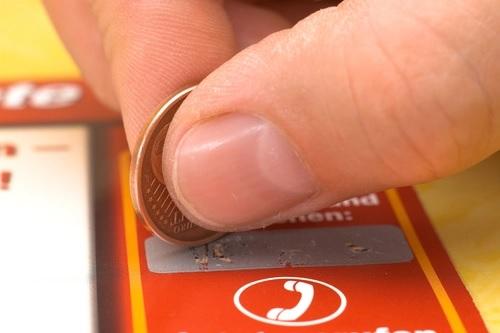Con una moneda se raspa la cubierta metálica de un billete de lotería (Shutterstock).