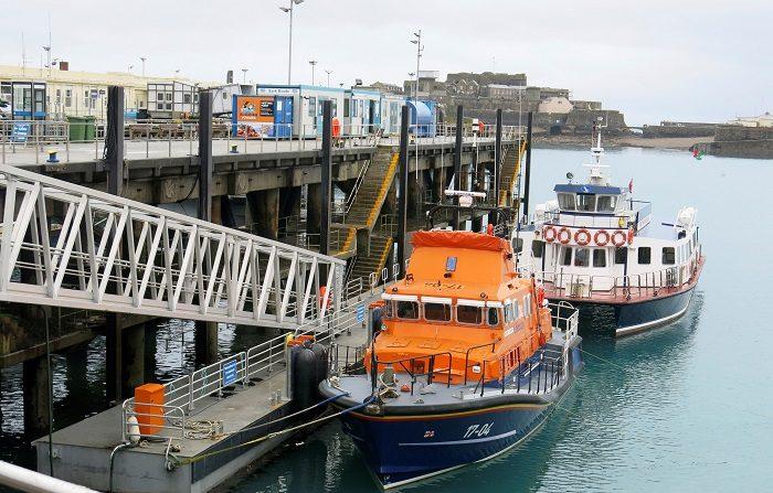 Uno de los barcos (color naranja) que participó los primeros días en las labores de búsqueda del futbolista Emiliano Sala permanece atracado este miércoles en el puerto de Guernsey en el Canal de la Mancha. EFE