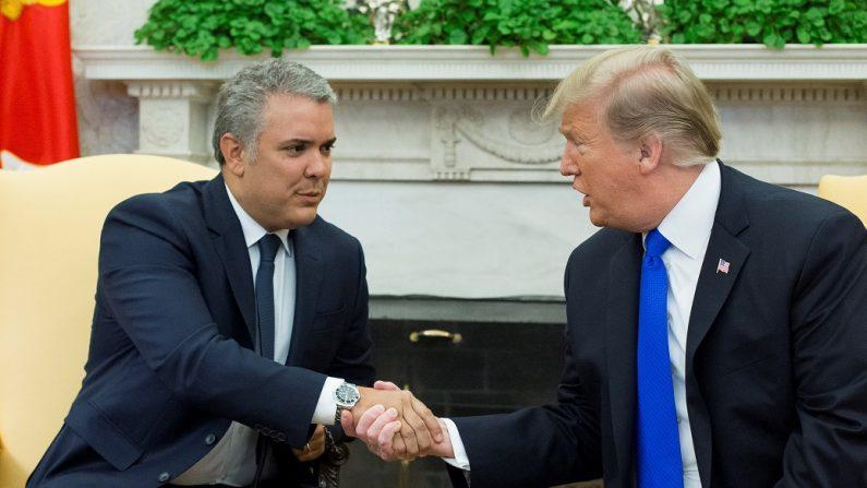 El presidente estadounidense, Donald Trump (d), estrecha la mano del presidente de Colombia, Iván Duque (i), este miércoles en el despacho Oval de la Casa Blanca, en Washington (Estados Unidos). EFE