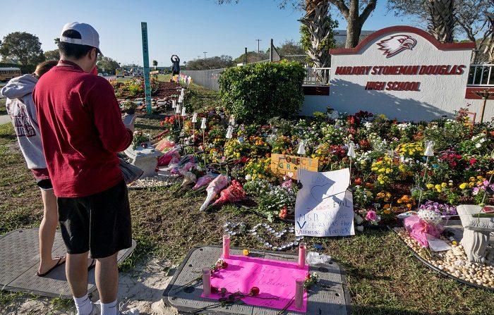 Dos personas fueron registradas este jueves al observar el monumento improvisado en conmemoración de las víctimas mortales del tiroteo de hace un año en el instituto Marjory Stoneman Douglas, en Parkland Florida (Estados Unidos). EFE/ Cristobal Herrera