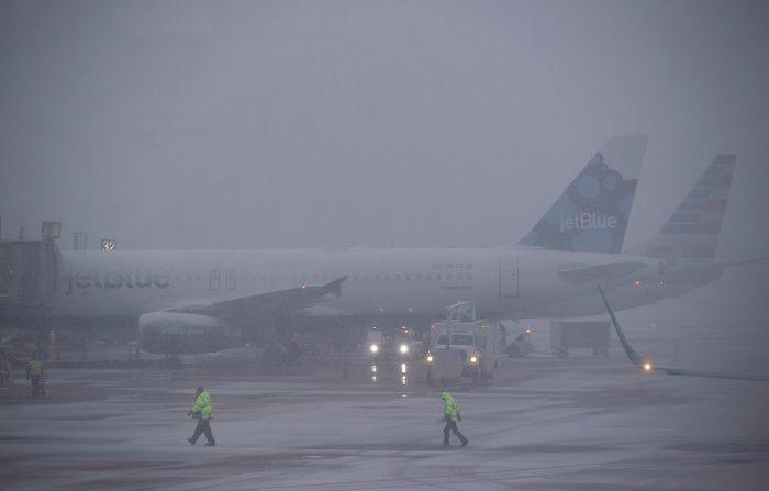 Varios trabajadores del aeropuerto asisten al despegue de un avión en Arlington, Virginia (Estados Unidos), este miércoles, durante una jornada de tormenta de nieve y bajas temperaturas. EFE/ Erik S. Lesser