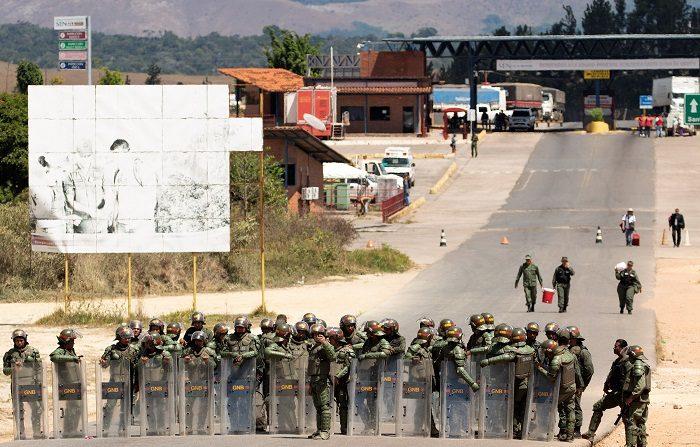 Miembros de la Guardia Nacional Bolivariana (GNB, policía militarizada) de Venezuela montan guardia este domingo en el paso fronterizo entre Brasil y Venezuela ubicado en la localidad de Pacaraima. EFE/Joédson Alves