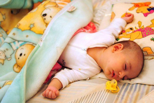 Un bebé duerme con su chupete a su lado. (Hamed Saber/Flickr/CC BY 2.0)