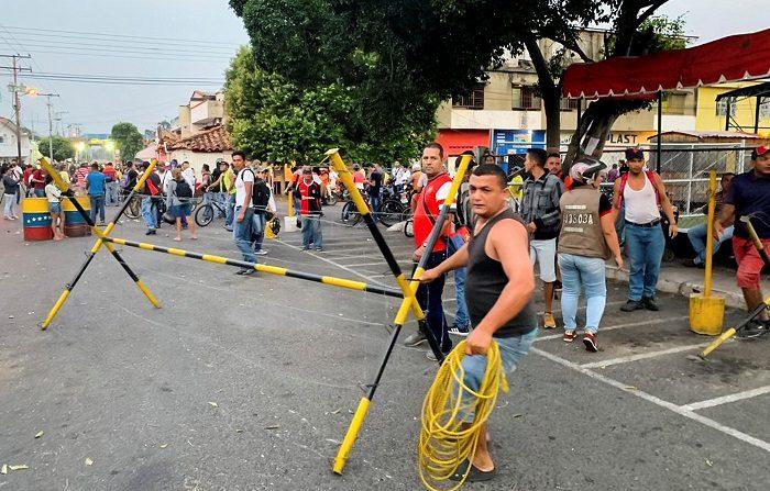 Un grupo de personas desarman las barreras de seguridad instaladas por la Guardia Nacional Bolivariana (GNB) que bloquean el paso al Puente Internacional Francisco de Paula Santander sobre el río Táchira, la segunda vía terrestre que comunica a Colombia con Venezuela, este sábado en la localidad de Ureña (Venezuela). EFE/HECTOR PEREIRA