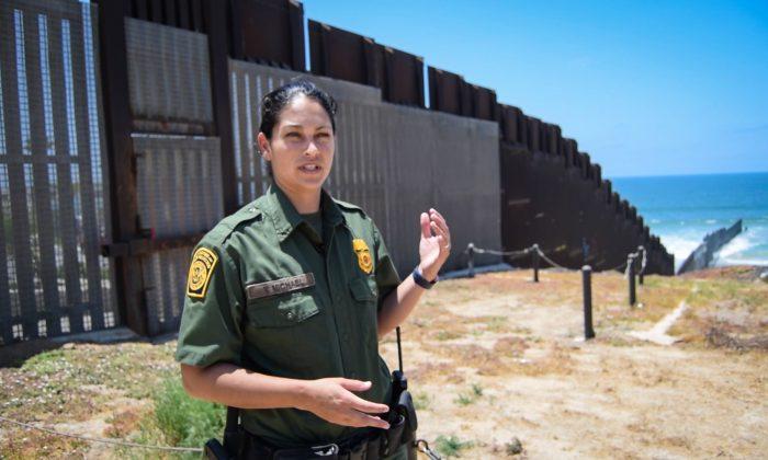 """Tekae Michael, agente de la Patrulla Fronteriza de San Diego, en el extremo occidental del muro fronterizo México-Estados Unidos en San Diego, California, el 12 de julio de 2018. La barrera """"PV-1"""" está diseñada para impedir que peatones y vehículos crucen ilegalmente la frontera. (Joshua Philipp/The Epoch Times)"""