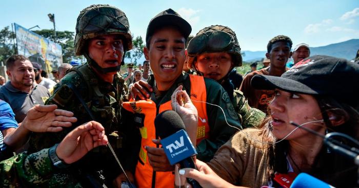 Soldados colombianos escoltan a un miembro de las Fuerzas Armadas Nacionales Bolivarianas de Venezuela que desertó a Colombia con su perro, en Cututa, el 25 de febrero de 2019. (Foto de LUIS ROBAYO/AFP/Getty Images)