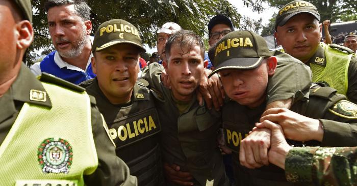 Policías colombianos acompañan a un policía venezolano que abandonó al régimen de Maduro en el puente internacional Simón Bolívar, en Cúcuta, Colombia, después de que el gobierno del presidente Nicolás Maduro ordenara el cierre temporal de la frontera con Colombia el 23 de febrero de 2019. (Foto de LUIS ROBAYO/AFP/Getty Images)