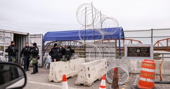 Oficiales del servicio de aduanas y protección fronteriza de EE. UU. aparecen junto a un cable de protección recién instalado a mitad del puente internacional Camino Real, desde Piedras Negras, México, hacia Eagle Pass, Texas, el 8 de febrero de 2019. (Charlotte Cuthbertson/La Gran Época)