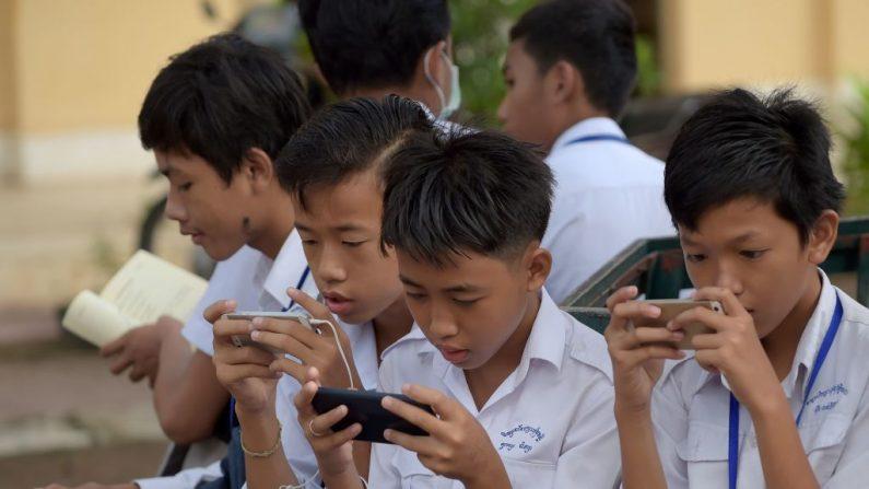 Esta foto tomada el 26 de junio de 2018 muestra a estudiantes usando teléfonos móviles en una escuela.. (TANG CHHIN SOTHY/AFP/Getty Images)