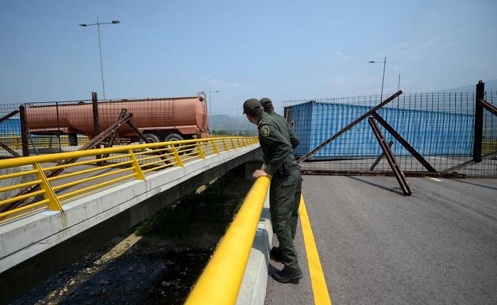 Policías colombianos miran el puente de las Tienditas, que une Táchira, Venezuela, y Cúcuta, Colombia, después de que fuera bloqueado con contenedores por las fuerzas de Venezuela, el 6 de febrero de 2019. (RAUL ARBOLEDA/AFP/Getty Images)