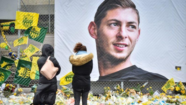 La gente mira las flores amarillas que se muestran frente al retrato del delantero argentino Emiliano Sala en el estadio Beaujoire en Nantes, el 8 de febrero de 2019. ( LOIC VENANCE/AFP/Getty Images)