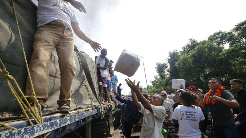 La gente trata de salvar la ayuda humanitaria después de que el camión que la transportaba fuera incendiado por las fuerzas del régimen de Maduro en el puente internacional Francisco de Paula Santander entre Cúcuta (Colombia) y Ureña (Venezuela), el 23 de febrero de 2019. (SCHNEYDER MENDOZA/AFP/Getty Images)