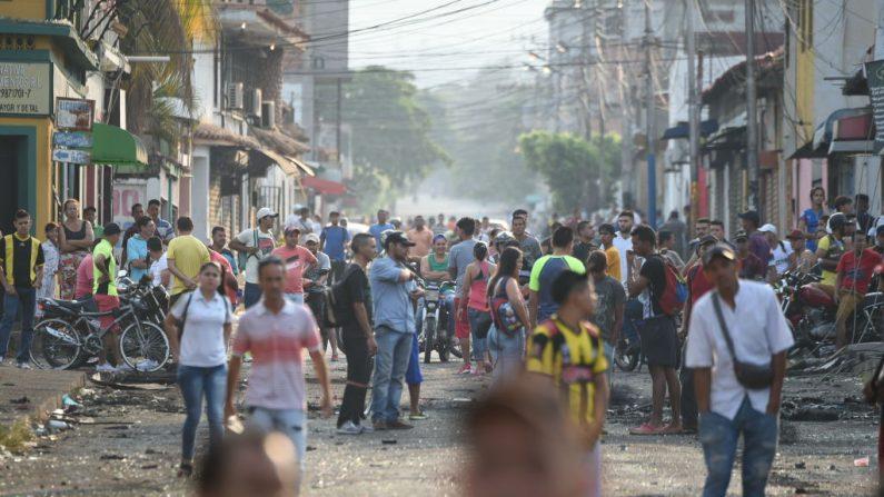 Venezolanos esperan cerca de la frontera entre Venezuela y Colombia en Ureña mientras el cruce entre ambos países permanece cerrado el 25 de febrero de 2019.(JUAN BARRETO/AFP/Getty Images)