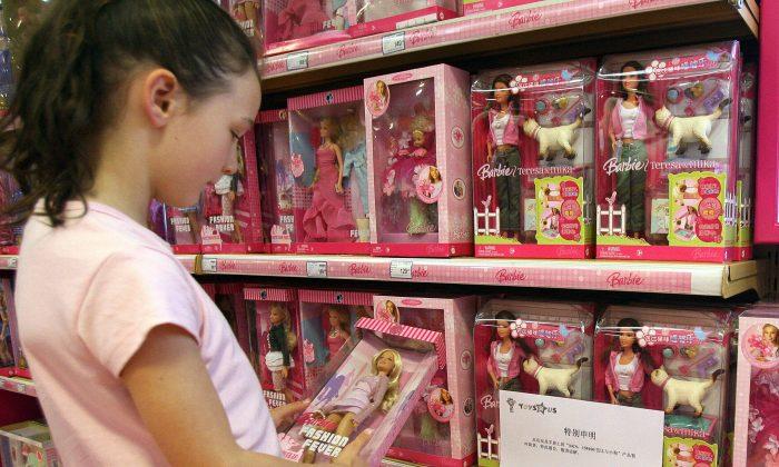 """Una niña sostiene una muñeca Barbie junto a un cartel que dice que la muñeca """"Barbie and Tanner"""", fabricado por el gigante de juguetes estadounidense Mattel, que acaba de ser retirado del mercado en los Estados Unidos, está agotado en una tienda de Toys `R' en Shanghai, el 15 de agosto de 2007. (MARK RALSTON/AFP/Getty Images)"""