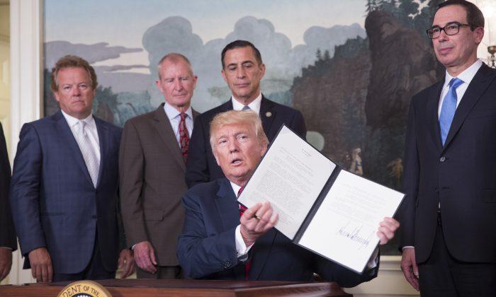 El presidente Donald J. Trump firma un memorando sobre  leyes, políticas, prácticas y acciones de China relacionadas con la propiedad intelectual, la innovación y la tecnología en la Casa Blanca, Washington, el 14 de agosto de 2017. (Chris Kleponis-Pool/Getty Images)