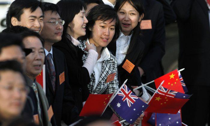 Residentes chinos esperan a que el exmandatario chino Hu Jintao llegue al aeropuerto internacional de Sydney el 5 de septiembre de 2007. (RICK STEVENS/AFP/Getty Images)
