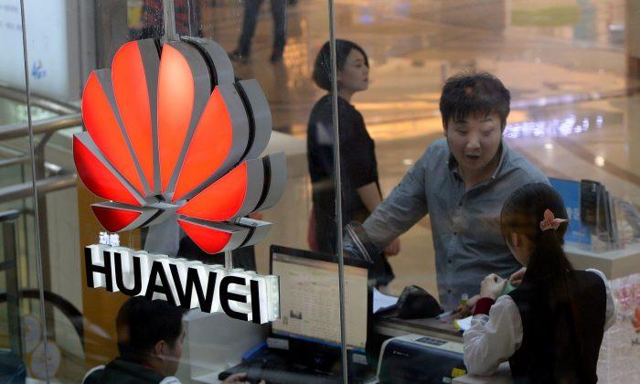 Una empleada utiliza una computadora mientras atiende un cliente en una tienda Huawei en Beijing, el 24 de marzo de 2014. (MARK RALSTON/AFP/Getty Images)