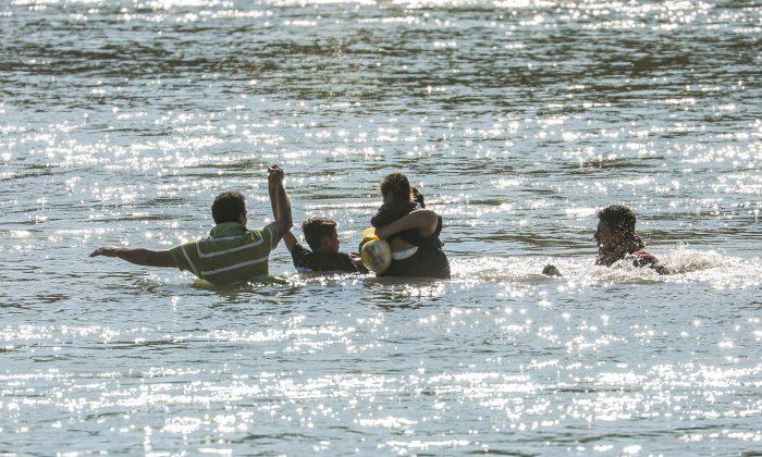 Los que cruzan ilegalmente la frontera son rescatados por agentes del Servicio de Aduanas y Protección Fronteriza de Estados Unidos cuando se quedan atascados a mitad de camino a través del Río Grande desde México hasta Eagle Pass, Texas, el 16 de febrero de 2019. (Charlotte Cuthbertson/The Epoch Times)