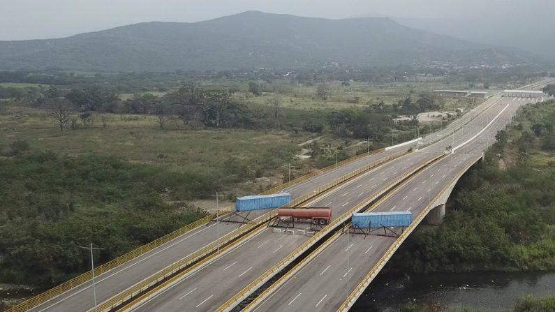 Un camión cisterna, contenedores y una valla improvisada bloquean el Puente Internacional Las Tienditas en un intento de impedir que la ayuda humanitaria entre desde Colombia, como se ve desde las afueras de Cúcuta, en la frontera de Colombia con Venezuela, el 6 de febrero de 2019. (Foto AP)