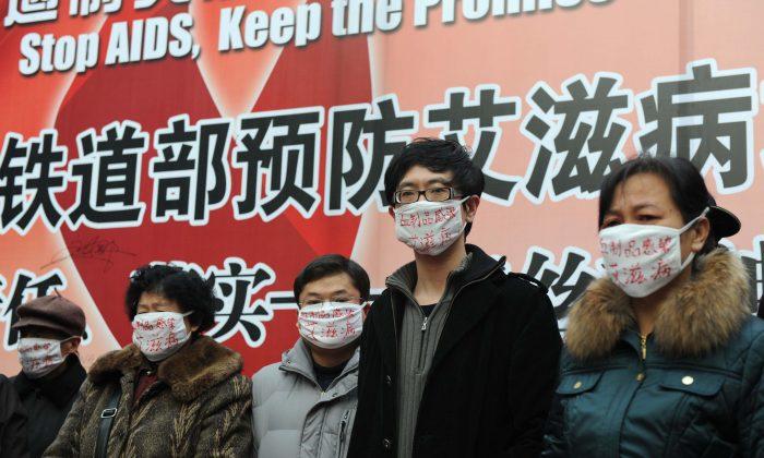 Manifestantes hemofílicos, todos los cuales contrajeron el VIH de productos sanguíneos infectados, usan mascarillas quirúrgicas durante un evento de concientización sobre el SIDA en el Día Mundial del SIDA en la estación ferroviaria del sur de Beijing el 1 de diciembre de 2009, para pedir un mejor apoyo del gobierno a las víctimas del VIH/SIDA en China. (AFP/Getty Images)