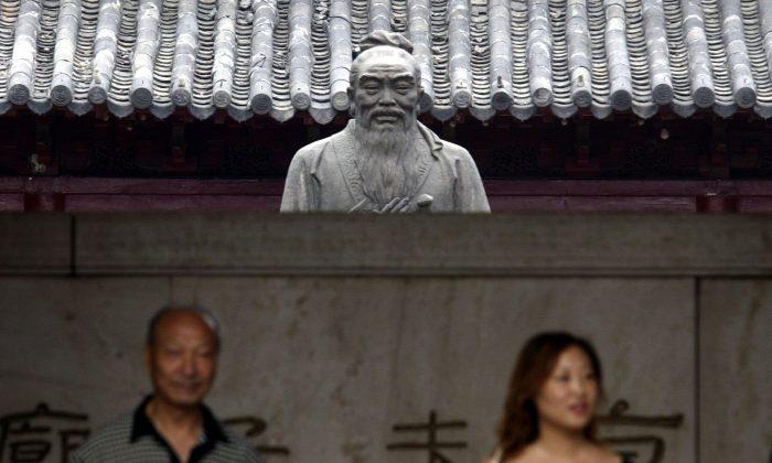 Turistas parados frente a una estatua de Confucio en Nanjing en la provincia de Jiangsu, China. (Fotos de China/Imágenes de Getty)