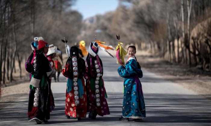 Niñas vestidas con trajes tradicionales tibetanos caminando por una carretera después de participar en un festival para celebrar el Año Nuevo Tibetano en la aldea de Douhoulou, a unos 50 km al sur de Guide en la meseta tibetana de Qinghai, el 25 de febrero de 2018. (JOHANNES EISELE/AFP/Getty Images)