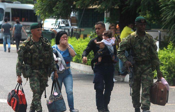 Soldados colombianos acompañan a un policía venezolano (c-d), que carga a su hija, y a su esposa (c-i), luego de cruzar a Cúcuta (Colombia). EFE/ Ernesto Guzman Jr.