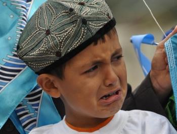 Un joven uigur en Calgary, Canadá, llora en una manifestación para protestar contra la represión del Partido Comunista en Xinjiang, China. (Jerry Wu/La Gran Época)