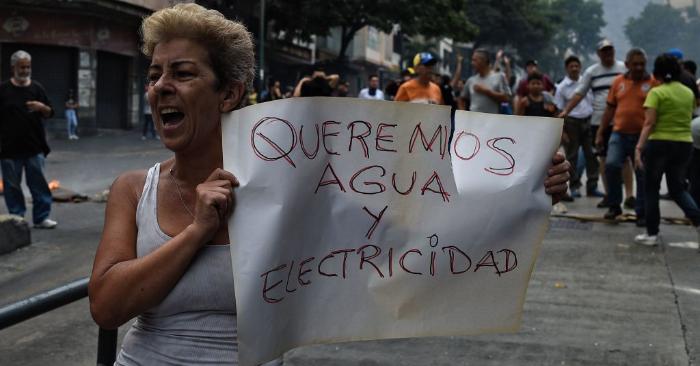 """Una mujer sostiene un cartel en el que reclama """"Queremos agua y electricidad"""" durante una protesta por la falta de agua y de servicio eléctrico, en la avenida Fuerzas Armadas de Caracas, el 31 de marzo de 2019. Foto de FEDERICO PARRA/AFP/Getty Images."""
