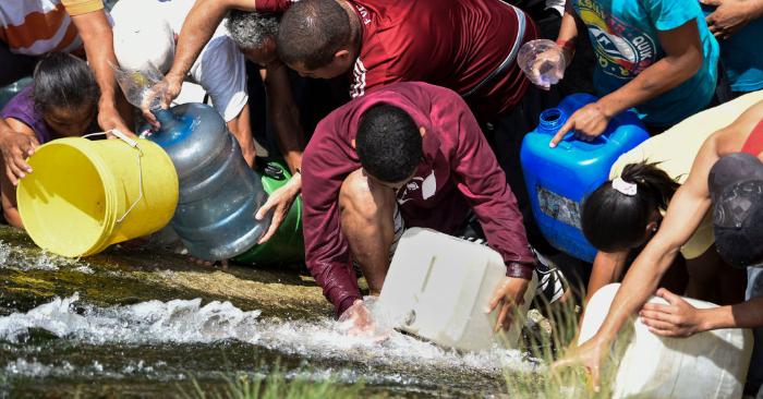La gente recoge agua de un canal de alcantarillado en el río Guaire en Caracas el 11 de marzo de 2019, mientras que un apagón masivo sigue afectando a algunas áreas del país. (Foto de JUAN BARRETO/AFP/Getty Images)