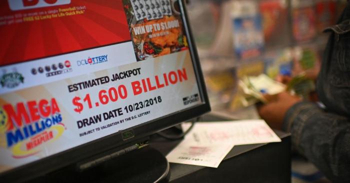 Personas comprando billetes de Mega Millions horas antes del sorteo del premio mayor de 1.500 millones de dólares, en una licorería en el centro de Washington DC, el 23 de octubre de 2018 (Foto de ERIC BARADAT/AFP/Getty Images)