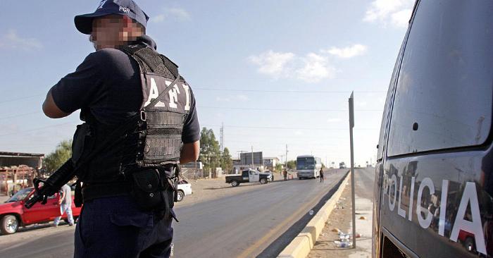 Un miembro de la policía estatal participa de un operativo de seguridad en una da las carreteras que llevan al puente internacional con Estados Unidos, en Nuevo Laredo, noreste de la capital mexicana, el 17 de junio de 2005. Foto de ALFREDO ESTRELLA/AFP/Getty Images.