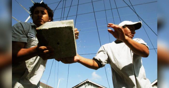 Los trabajadores migrantes José (D) de México, y Christian de Honduras, realizan trabajos de 'nivelación' en una casa dañada por el huracán Katrina, el 27 de abril de 2006, en Nueva Orleáns. (Mario Tama/Getty Images)