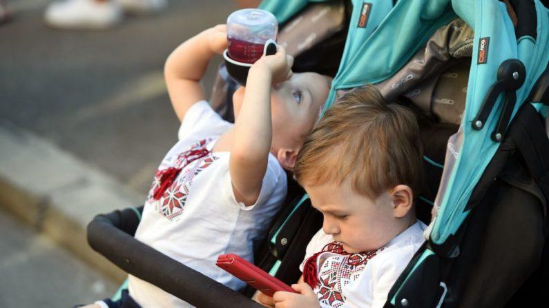 Imagen de archivo. Un bebé juega con el teléfono móvil mientras su hermano gemelo toma jugo mientras asisten al Festival Of Twins, en Kiev, el 11 de agosto de 2018. (SERGEI SUPINSKY/AFP/Getty Images)