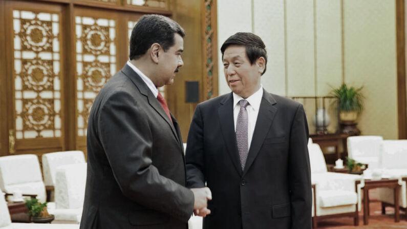 El dictador venezolano Nicolás Maduro (izq) estrecha la mano del presidente del Comité Permanente del Congreso Nacional del Pueblo de China, Li Zhanshu, el 14 de septiembre de 2018. (MARCELO GARCIA/AFP/Getty Images)